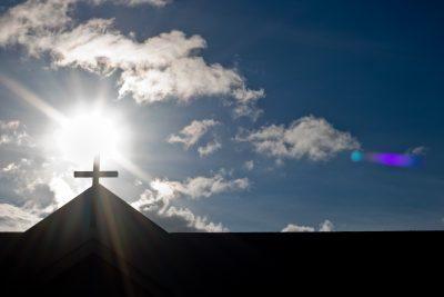 blue sky on cross.Cristian cross on a little church with sun in backlight.