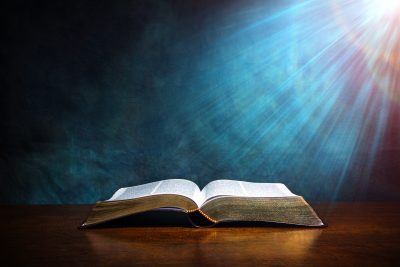 Open Bible on a wood table with light coming from above. ( Church concept. )